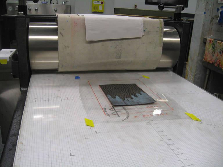 The plate, centered in the template on the press bed.